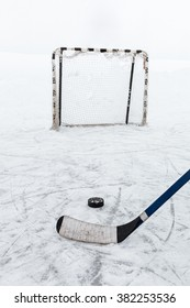 Hockey stick and puck on the ice of public hockey ring opposite the gate