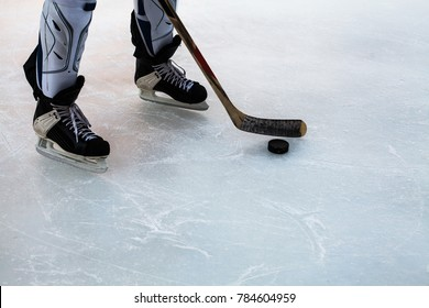 Hockey stick and puck on natural ice. Legs of hockey player.