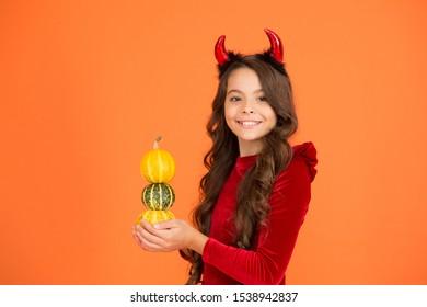 Hocus pocus with pumpkin. Happy girl hold pumpkin stack orange background. Little child with red devil horns make pumpkin trick. Halloween pumpkin. Jack o lantern. Autumn holidays celebration.
