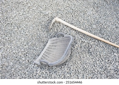 Hoe and clam-shell shaped basket on pile crushed stone at construction site