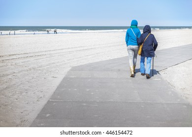 HOEK VAN HOLLAND, THE NETHERLANDS - MAY 2, 2015: Daughter supports her elderly mother at a walk on the beach