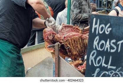 Hog Roast Street Food Market Vendor. Carving Roasting Pig