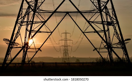 Hoggeston, Aylesbury Vale, Bucks, UK - Sept 15th 2020 : National Grid Electricity Pylons and power lines silhouette to horizon on agricultural land at dawn with  atmospheric sunrise.