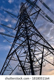 Hoggeston, Aylesbury Vale, Bucks, UK - Sept 15th 2020 : Electricity pylon tower partial silhouette photographed from below looking up at sunrise with blue sky and clouds.