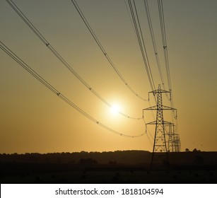 Hoggeston, Aylesbury Vale, Bucks, UK - Sept 15th 2020 : National Grid electricity power lines lead to a row of silhouette pylons at sunrise in Buckinghamshire.