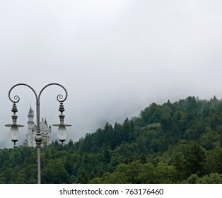 Hohenschwangau, Bavaria/Germany - August 8, 2017: Neuschwanstein castle behind an ornate lamppost on a foggy morning