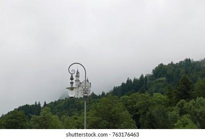 Hohenschwangau, Bavaria/Germany - August 8, 2017: Neuschwanstein castle behind an ornate lamppost on a foggy morning