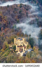 Hohenschwangau bavarian castle old yellow building aerial view with a beautiful fog on the forest in autumn season