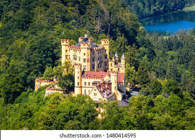 Hohenschwangau Castle near Fussen, Bavaria, Germany. This castle is a landmark of German Alps. Aerial scenic view of famous castle in Hohenschwangau district. Alpine mountain landscape in summer.