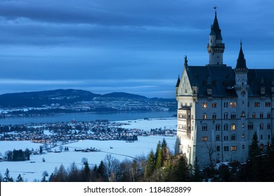 HOHENSCHWANGAU / GERMANY, DECEMBER 1st, 2007: Part of Neuschwanstein Castle in winter at Dusk with the village of Schwangau in the background