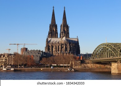 The Hohenzollern bridge over Rhine river on a sunny day. The Cologne Cathedral (Kolner Dom) in the city of Cologne, Germany. It is the largest Gothic church in northern Europe. - Shutterstock ID 1834342033