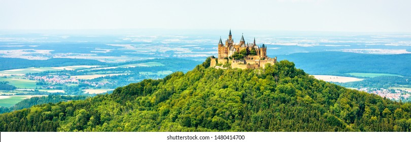 Hohenzollern Castle on mountain top, Germany. This castle is a famous landmark in vicinity of Stuttgart. Panoramic view of Burg Hohenzollern in summer. Landscape of Swabian Alps with Gothic castle.