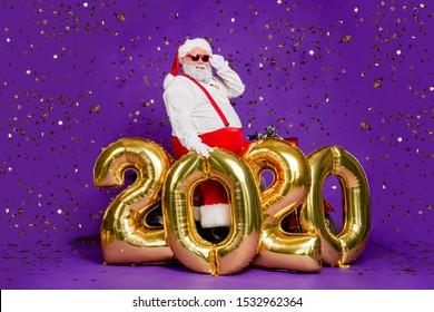 Ho-ho-ho! Full body photo of santa man sit on motorbike big air newyear 2020 balloons saying congratulations wear sun specs x-mas costume isolated purple background