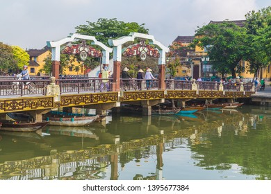 HOI AN - 25TH MARCH 2017: A bridge over the Thu Bon River connecting to the Ancient Town during the day. People can be seen on the bridge