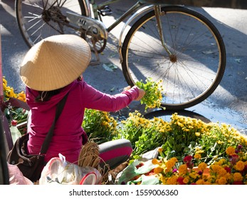 Hoi An, Quang Nam Province, Vietnam - September 23, 2018: Vietnamese woman wearing a conical straw hat or non la and a pink hooded sweatshirt selling gold and red chrysanthemums at an outdoor market.