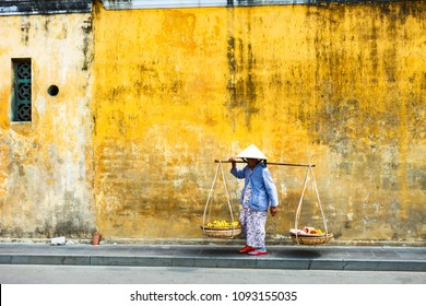 HOI AN, QUANG NAM, VIETNAM, April 26th, 2018:Vietnamese woman street seller In hoi an Vietnam in ancient town Hoi An with view of typical yellow houses