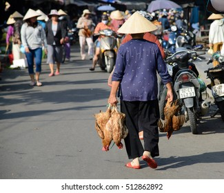 Hoi An, Vietnam - 20 October 2016: Old lady carrying chickens through Hoi An Old Town market, Vietnam