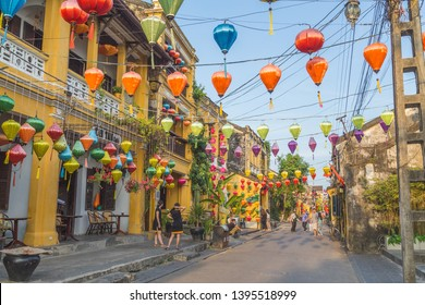 HOI AN, VIETNAM - 24TH MARCH 2017:  Colourful architecture and lanterns along streets of Hoi An Ancient Town during the day. People can be seen.