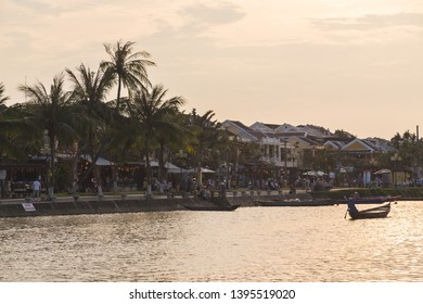 HOI AN, VIETNAM - 24TH MARCH 2017: Lots of people in boats along the Thu Bon river in Hoi An at sunset. Buildings can be seen along the river bank.