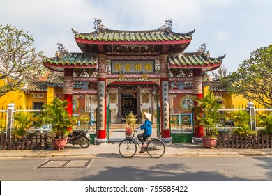 HOI AN, VIETNAM - 25TH MARCH 2017: The outside of the Trieu Chau Assembly Hall in Hoi An, Vietnam during the day. A person with a traditional conical hat can be seen going past on a bike.