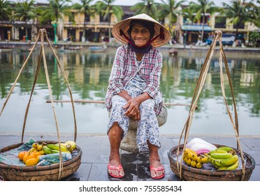 HOI AN, VIETNAM - 27TH MARCH 2017: An elderly lady waiting by the side of the river in Hoi An selling to sell fruit.