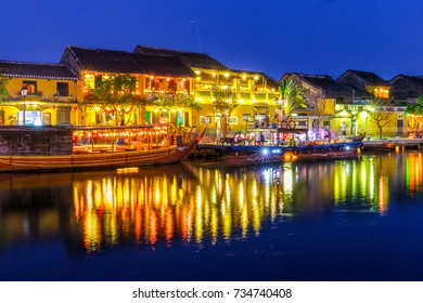 HOI AN, VIETNAM - 4/19/2016: Lights from Hoi An, Vietnam riverside cafes and shops reflect off the water.
