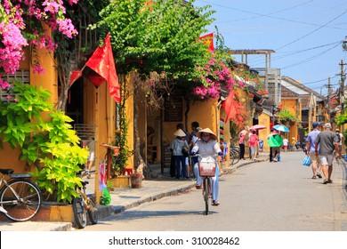 HOI AN, VIETNAM - APIRL 14: An unidentified woman rides her bicycle on Apirl 14, 2014 in Hoi An, Vietnam. Hoi An, a UNESCO World Heritage site, is a major touristic destination in Central Vietnam.