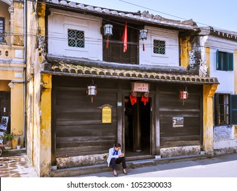 Hoi An, Vietnam - Apr. 13, 2011: Woman waits outside the old historic Tan Ky House, house that was certified as part of Hoi An's national heritage.