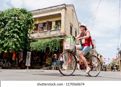 Hoi An, Vietnam - August 18, 2018 : Tourist ride bicycle on the street of Hoi An ancient town. Hoi An is the World's Cultural heritage site.