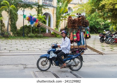 HOI AN, VIETNAM - AUGUST 3 2013: A brush salesman drives through the streets of Hoi An selling his wares