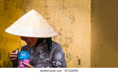 Hoi An, Vietnam - December 4, 2012: Old poor woman wearing conical hat and traditional asian dress. Vietnamese lady holding pink and blue jar. Wrinkled face under headwear. Elderly person standing nea