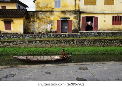 HOI AN, VIETNAM - FEB 3 - 2015 - Old man paddles his boat in a canal,   Hoi An, Vietnam