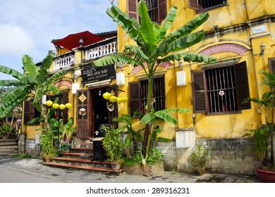 HOI AN, VIETNAM - FEB 3, 2015 - Traditional yellow ochre building with palm trees, Hoi An, Vietnam