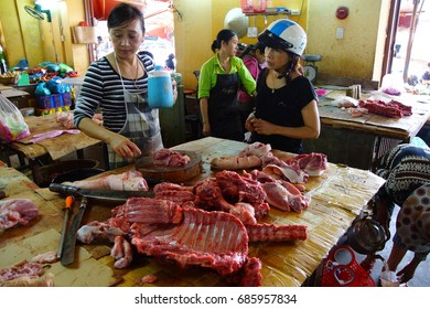 HOI AN, VIETNAM - FEB 3, 2015 - Preparing meat for sale in the market of  Hoi An, Vietnam