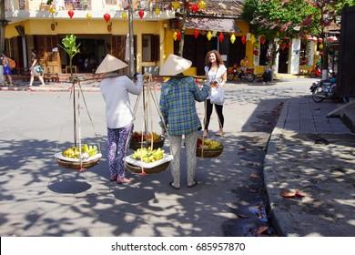 HOI AN, VIETNAM - FEB 3 - 2015 - Two women carrying fruit stop for a woman photographer,  Hoi An, Vietnam