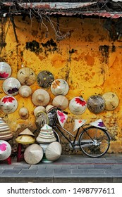 """Hoi An, Vietnam - February 1, 2018: Bicycle against a yellow wall with non la, the conic vietnamese bamboo hats for sale in the ancient UNESCO town. Some of the hats read """"Vietnam Travel"""""""