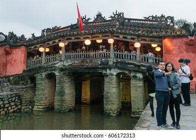 HOI AN, VIETNAM - FEBRUARY 11, 2017: Japanese Covered Bridge in Hoi An, Vietnam. Tourists are taking photos around the bridge constructed in the 1590s.  Hoi An  is a UNESCO World Heritage Site.