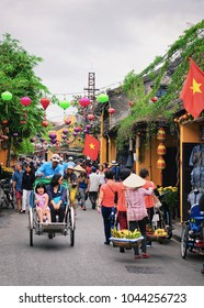 Hoi An, Vietnam - February 17, 2016: Tourists on cycle rickshaws in the street of old city of Hoi An, Vietnam