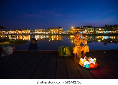 HOI AN, VIETNAM - JAN 7, 2014: Unidentified Vietnamese girl sells floating candles on Hoi An bridge at night.