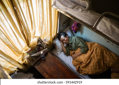 HOI AN, VIETNAM - JAN 7, 2014 - Man sleeps on vietnamese sleeper train bed