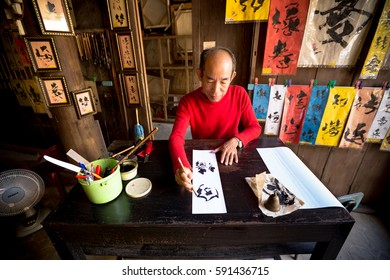 HOI AN, VIETNAM - JAN 8: Local calligrapher creates new art works in his shop in Hoi An, Vietnam on January 8, 2014.