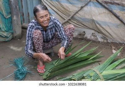 Hoi An, Vietnam - January 22,2018: smiling Vietnamese woman squatting down while she sews leaves together to make thatched roofs for huts.