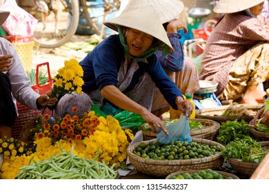 HOI AN, VIETNAM - JANUARY 6, 2010: Vietnamese street vendors selling vegetables at local market in Hoi An