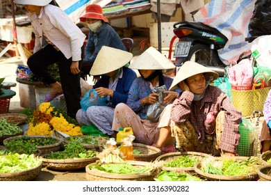 HOI AN, VIETNAM - JANUARY 6, 2010: Vietnamese street vendors sell fresh vegetables at local market in Hoi An