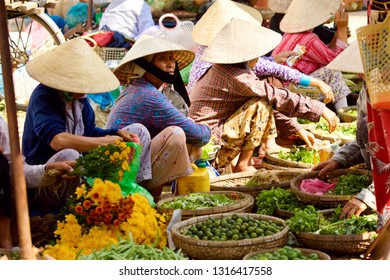 HOI AN, VIETNAM - JANUARY 6, 2010: Vietnamese steet vendors sell fruits and vegetables at local market in Hoi An