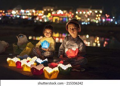 HOI AN, VIETNAM - JANUARY 6, 2014: Two small kids selling handmade lanterns to tourists in the streets of old city. Tradition says, that  wishes come true, if you let the lanterns swim.