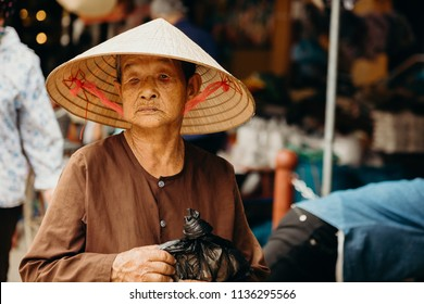Hoi An, Vietnam / Vietnam - July 27 2013: Old Vietnamese woman selling at Hoi An street market