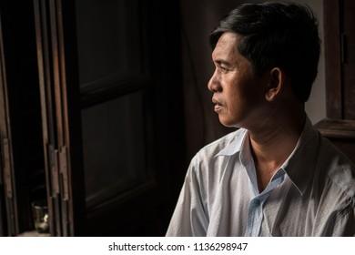 Hoi An, Vietnam / Vietnam - July 27 2013: Asian man looking through a window