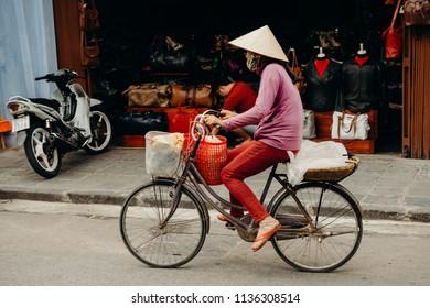 Hoi An, Vietnam / Vietnam - July 27 2013: Vietnamese woman riding her bike through the streets of Hoi An