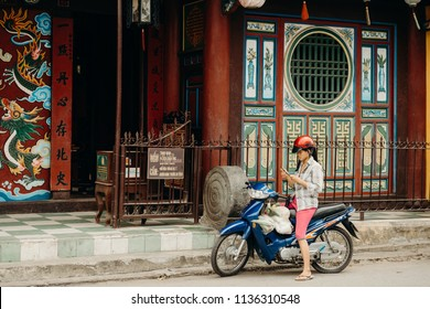 Hoi An, Vietnam / Vietnam - July 27 2013: Vietnamese woman on her motorcycle in front of a typical asian building